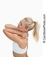 Side view of sporty young woman massaging neck