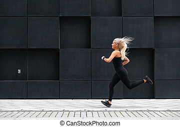 Side view of sporty young woman running fast in minimalist urban environment