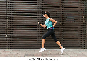 Side view of sporty young woman running on a sidewalk.