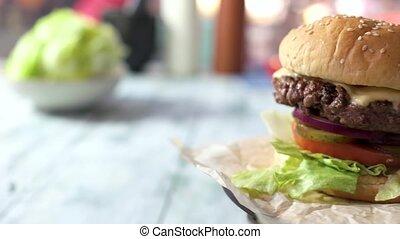 Side view of tasty cheeseburger. Rotating burger closeup....