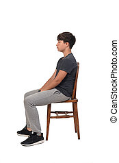 side view of teenage boy sitting on a chair with white background,looking at the side