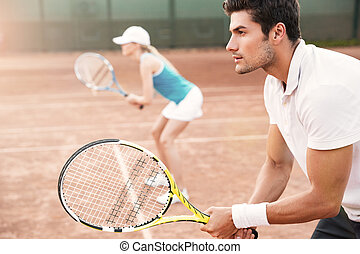 Side view of tennis man and woman. woman on background