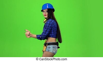 Side view of the girl moving vigorously on a green background. Slow motion
