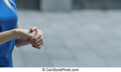 Side view of the girl's hands sprinkled with alcohol antiseptic for disinfection. Corona virus health protection concept. Slow motion. Close up outdoors on a street background.