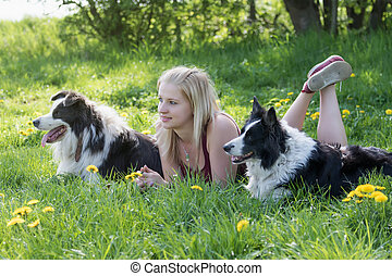 Side view of the young blond woman lying between two Border Collies