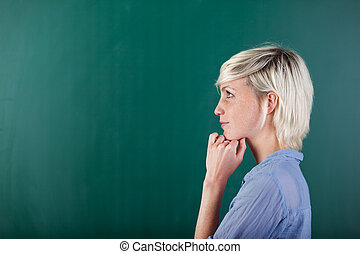 Side View Of Thoughtful Blond Woman By Chalkboard