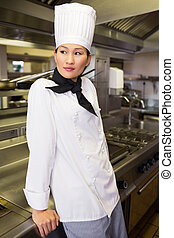 Side view of thoughtful female cook in kitchen