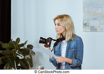side view of thoughtful photographer with photo camera and photoshoot example