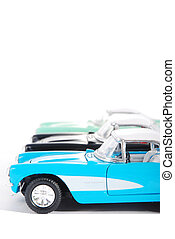 Side view of three retro toy cars on white background