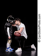Side view of trainer instructing boy american football player