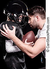 trainer instructing boy american football player