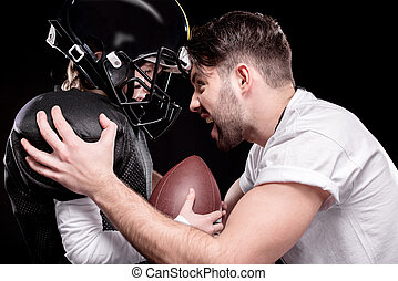 trainer screaming at boy american football player on black