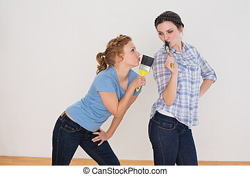 Side view of two cheerful female friends singing into paintbrushes in a new house