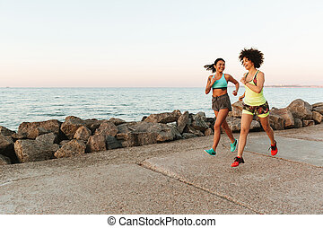 Side view of two fitness women running outdoors