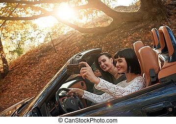 Side view of two happy women friends in cabliolet, making selfie