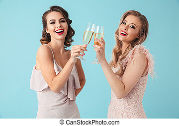 Side view of Two happy women in dresses drinking champagne