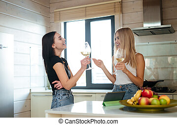 Side view of two laughing women drinking wine