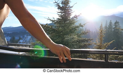 Side view of unrecognizable athletic guy standing on balcony and looking at beautiful nature on sunny day. Young man enjoying winter vacation or holiday. Beautiful landscape. Close up Slow motion