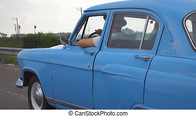 Side view of unrecognizable man in hats driving at blue retro car after rain during summer travel. Young guy moving at his old vintage vehicle on highway. Slow motion Close up