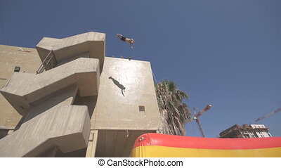 Side view of unrecognizable man jumping from high building and falling down in an inflatable trampoline at sunny day. Concept of healthy lifestyle. Close up Slow motion