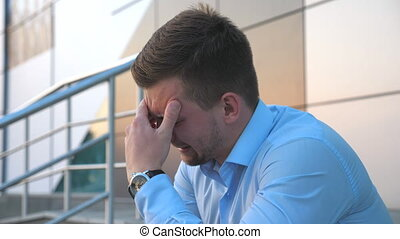 Side view of upset sad businessman sitting on stairs near office building and crying. Desperate young man got a very bad news and feeling despair outdoor. Concept of financial crisis. Close up