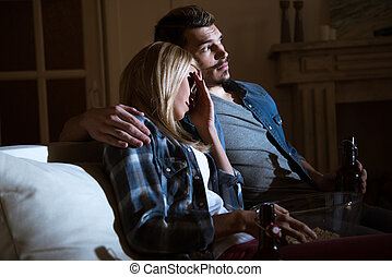 woman closing eyes while watching movie with man