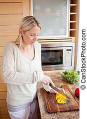 Side view of woman cutting vegetables