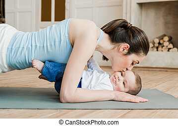Side view of woman doing plank exercise and kissing her son