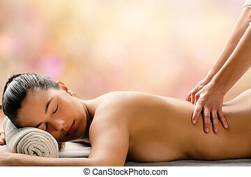 Side view of woman having hot oil massage is spa.