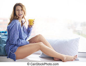 Side view of woman in pajamas sitting on the bed