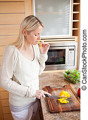 Side view of woman nibbling while cutting vegetables
