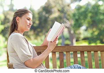 Side view of woman reading while sitting on a park bench
