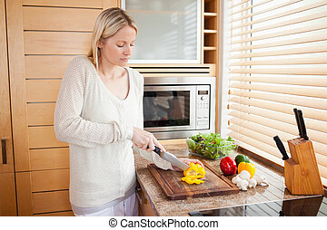 Side view of woman slicing bell pepper