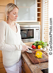 Side view of woman slicing vegetables for her salad