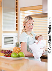 Side view of woman standing in the kitchen with her baby on her arms