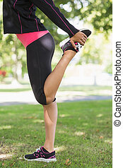 Side view of woman stretching her leg during exercise at park