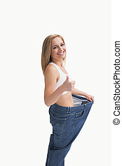 Side view of woman wearing old pants after losing weight and gesturing thumbs up over white background