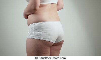 Side view of woman with fat belly. Obesity concept.