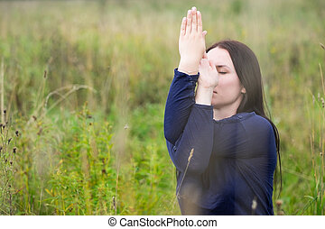 Side view of woman with her crossed arms performing yoga...