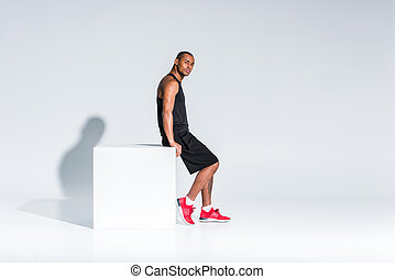 side view of young african american sportsman in sportswear sitting and looking at camera on grey