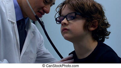 Side view of young asian male doctor examining caucasian boy patient chest in a clinic 4k