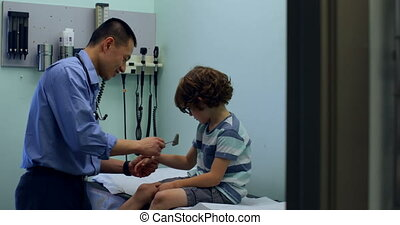 Side view of young asian male doctor examining caucasian boy patient hand in a clinic 4k