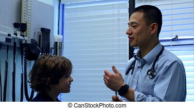 Side view of young asian male doctor showing tuning fork to ...
