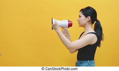 Side view of young asian woman shouting in loudspeaker. Protest or announcement concept. High quality 4k footage