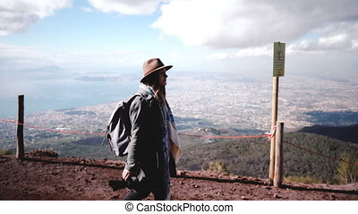 Side view of young beautiful female tourist with backpack hiking down from Vesuvius volcano enjoying view of Naples. Happy cheerful traveler businesswoman walking along a mountain road on vacation.