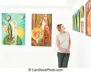 side view of young beautiful woman standing in an art gallery contemplating paintings displayed in front of her