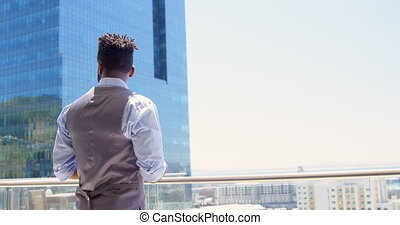 Side view of young black businessman texting on mobile phone...
