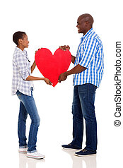 young black couple holding heart symbol