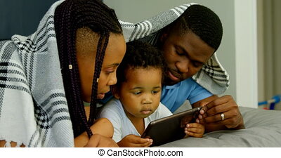 Side view of young black family using digital tablet on bed in bedroom of comfortable home 4k