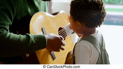 Side view of young black father and little son playing guitar in living room of comfortable home 4k